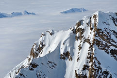 Vista dei picchi ricoperti neve sopra le nuvole Fotografie Stock Libere da Diritti
