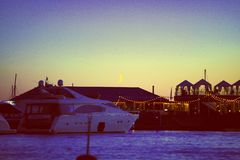 Vista dei pilastri dell'yacht e della luna , vita notturna e ristoranti sull'acqua fotografia stock