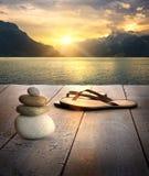 Vista dei sandali e delle rocce sul bacino fotografia stock