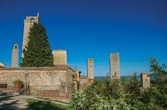Vista dei tetti e delle torri con gli alberi e del cielo soleggiato blu a San Gimignano Fotografia Stock