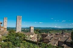 Vista dei tetti e delle torri con le colline verdi nei precedenti a San Gimignano Fotografie Stock Libere da Diritti
