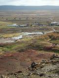 Vista del área geotérmica del géiser en el valle de Haukadalur, Islandia, con las pequeñas figuras de la gente que se reúne para  fotos de archivo