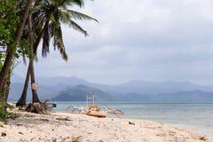 Vista del barco en la playa con las palmeras En el fondo de la isla Foto de archivo libre de regalías