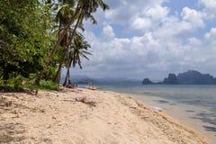 Vista del barco en la playa con las palmeras En el fondo de la isla Imagen de archivo libre de regalías