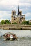 Vista del barco turístico y del Notre-Dame de Paris Imagen de archivo libre de regalías