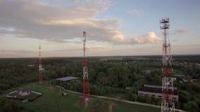 Vista del bosque, de las casas de campo y de las estaciones base contra el cielo azul con las nubes en luz del día en el verano,  metrajes