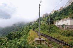 Vista del bosque y de casas alrededor de vías del tren en día nublado y de niebla Cerca del lago de Albano Foto de archivo libre de regalías