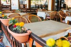 Vista del caffè aperto vuoto di estate con le sedie di vimini e della mobilia di legno accanto ai vasi con le piante ed i fiori Fotografia Stock