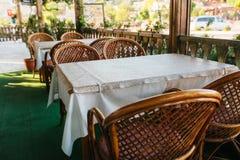 Vista del caffè aperto vuoto di estate con le sedie di vimini e della mobilia di legno accanto ai vasi con le piante ed i fiori Fotografie Stock