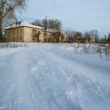 Vista del camino del invierno y de la casa beige dos-storeyed vieja Imagen de archivo libre de regalías