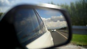 Vista del camino en el espejo retrovisor de un coche en el camino recto del verano - desfile de automóviles de la boda metrajes