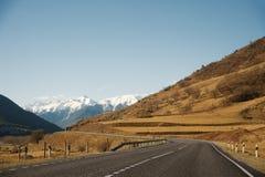 Vista del camino del otoño que lleva a las montañas a los picos coronados de nieve del Cáucaso El concepto de viajar a Imagen de archivo