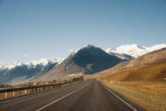 Vista del camino del otoño que lleva a las montañas a los picos coronados de nieve del Cáucaso El concepto de viajar a Foto de archivo libre de regalías