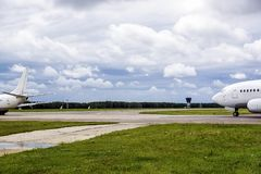 Vista del campo del despegue y de dos aviones que van en una pista por tarde nublada del verano Fotos de archivo libres de regalías