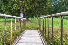 Vista del campo en Sunny Summer Day con el puente del metal en marco, concepto de paz y armonía fotos de archivo libres de regalías