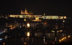 Vista del castello di Praga attraverso il fiume la Moldava alla notte Fotografie Stock Libere da Diritti