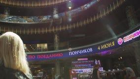 Vista del centro comercial Visitantes que se sientan en sillas acontecimiento asoleado Muchos pisos almacen de metraje de vídeo