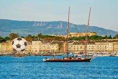Vista del centro histórico de Ginebra con una bola y un yate grandes del fútbol con la gente en el lago geneva Suiza Fotos de archivo libres de regalías