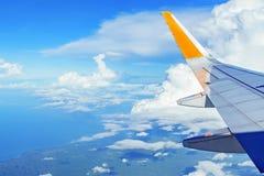 Vista del cielo azul y de la tierra nublados del ala del aeroplano de la ventana Fotos de archivo libres de regalías