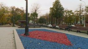 Vista del cuadrado con el macizo de flores, los bancos y los árboles el día del otoño metrajes