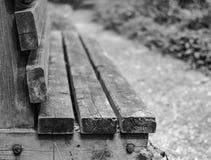 Vista del dettaglio di legno di rappresentazione del banco di parco dei legnami, visto da un sentiero per pedoni vuoto Fotografie Stock