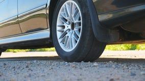 Vista del dettaglio sulla ruota dell'automobile potente che inizia movimento e che slitta sulla strada asfaltata Piccole pietre e archivi video