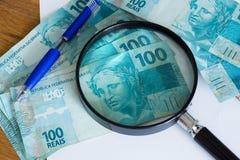 Vista del dinero brasileño, de los reais, del arriba nominales con una hoja de papel y una pluma para los cálculos fotos de archivo libres de regalías