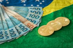 Vista del dinero y de los bitcoins brasileños contra la bandera brasileña fotografía de archivo