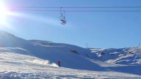 Vista del esquí de mudanza del remonte y del hombre de la montaña nevosa en fondo almacen de video