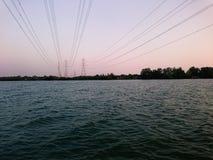 Vista del fiume con la linea incrocio di distribuzione di energia il fiume Fotografia Stock