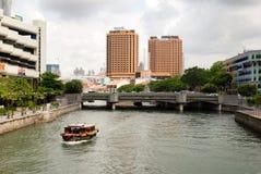 Vista del fiume di Singapore con una barca che passa vicino Immagine Stock