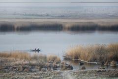 Vista del fiume, su cui i pescatori navigano in una barca immagini stock libere da diritti