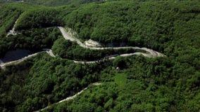 Vista del fuco di una depressione curva della strada di avvolgimento le montagne stock footage