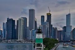 Vista del horizonte de Chicago en el fondo, faro en primero plano, con el lago Michigan en izquierda con los veleros en puerto foto de archivo libre de regalías
