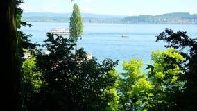 Vista del horizonte del lago de detrás los arbustos En la distancia puede ser visto como nave amarrada con los turistas Fotos de archivo libres de regalías