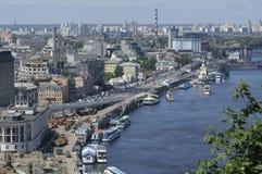 Vista del lado derecho del r?o de Dnieper, de la orilla, de edificios y del puerto fluvial, barco de placer que flota en el agua fotos de archivo libres de regalías
