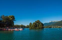 Vista del lago annecy, con l'isola, la vegetazione, i crogioli di pagaia e le montagne Fotografia Stock Libera da Diritti