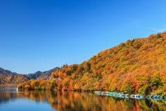 Vista del lago Chuzenji en la estación del otoño con agua de la reflexión adentro Imagenes de archivo