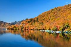 Vista del lago Chuzenji en la estación del otoño con agua de la reflexión adentro foto de archivo
