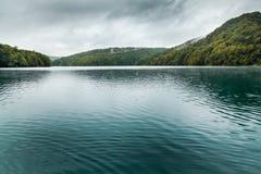 Vista del lago con agua oscura de la turquesa con las pequeños ondas y moun Imagen de archivo libre de regalías
