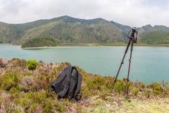 Vista del lago con i pali di trekking e dello zaino immagini stock