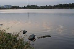Vista del lago dalla banca con piccole roccia e linea costiera Immagini Stock