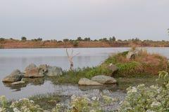 Vista del lago dalla banca con piccole roccia e linea costiera Fotografie Stock Libere da Diritti