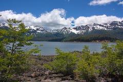 Vista del lago e delle montagne innevate Fotografie Stock