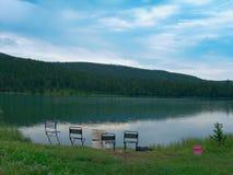 Vista del lago nella priorità alta delle sedie e della canna da pesca turistiche Immagine Stock