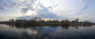 Vista del lago sunset con il contesto del villaggio Immagine Stock
