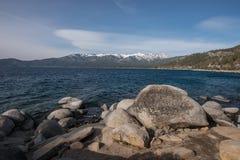Vista del lago Tahoe con le nevi sui picchi di montagna distanti e le rocce nella priorità alta Fotografia Stock Libera da Diritti