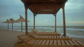 Vista del mar de la mañana a través del gazebo de la playa con los sunbeds de madera metrajes