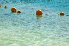 Vista del mar de una orilla con una larga cola de la flotación de color naranja de las boyas del marcador imagenes de archivo