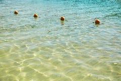 Vista del mar de una orilla con una larga cola de la flotación de color naranja de las boyas del marcador foto de archivo